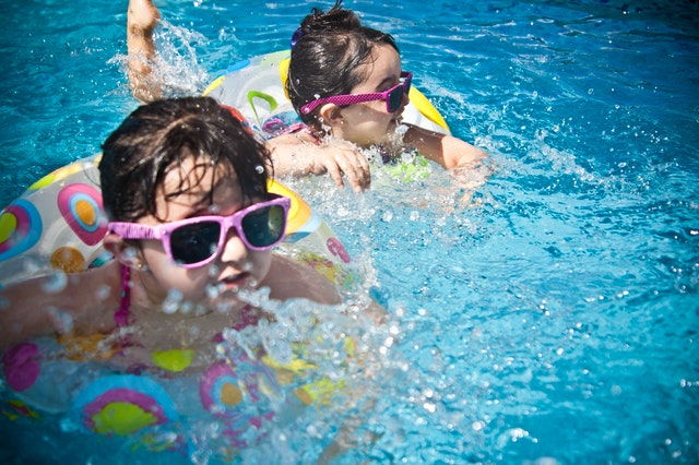 two children swimming in a pool with goggles and floaties in the summer sun
